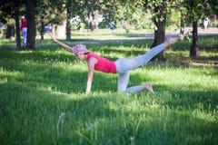 Femme attirante faisant le yoga en parc, mode de vie actif Le concept d'un mode de vie sain et d'une récréation active Images libres de droits