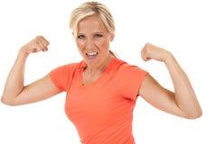 Femme attirante fléchissant ses bras dans un dessus orange Image libre de droits