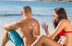 Femme attirante gaie appliquant la crème du soleil sur ses amis b Photographie stock libre de droits