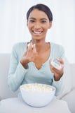 Femme attirante gaie mangeant du maïs éclaté tout en regardant la TV Images stock