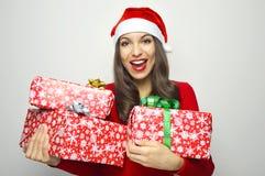 Femme attirante gaie souriant avec le chapeau de Santa Claus tenant des cadeaux de Noël sur le fond blanc Images libres de droits