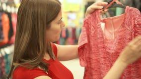 Femme attirante heureuse dans des achats rouges de T-shirt dans des vêtements de achat de mail Concept de shopaholism de consomma banque de vidéos
