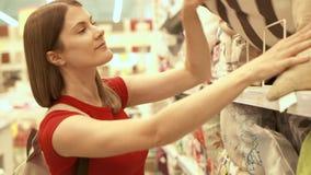 Femme attirante heureuse dans des achats rouges de T-shirt dans l'oreiller de achat de mail Concept de shopaholism de consommatio clips vidéos