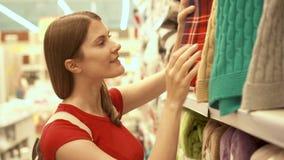 Femme attirante heureuse dans des achats rouges de T-shirt dans le plaid de achat de mail Concept de shopaholism de consommationi banque de vidéos