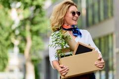 femme attirante heureuse tenant la boîte de papier avec la substance de bureau images stock