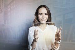 Femme attirante heureuse tenant un comprimé Photographie stock libre de droits