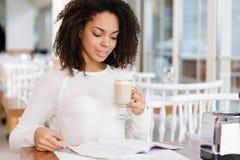 Femme attirante lisant un magazine tout en buvant Photo libre de droits