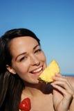 Femme attirante mangeant du fruit Photos stock