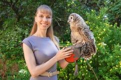 Femme attirante posant dans la robe grise avec un hibou sur son bras photo stock