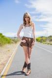 Femme attirante posant tout en faisant de l'auto-stop Photographie stock libre de droits