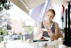 Femme attirante prenant la photo d'une pâtisserie sur elle Image stock