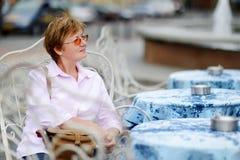 Femme attirante s'asseyant en café extérieur Photos stock