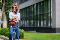 femme attirante s'asseyant sur le vélo avec les bras croisés images stock