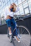 femme attirante s'asseyant sur le vélo et tenant le café dans la tasse de papier photos stock