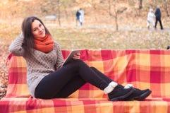 Femme attirante s'asseyant sur un banc avec un comprimé Photos stock