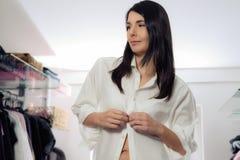 Femme attirante s'habillant dans un vestiaire image stock