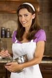 Femme attirante se mélangeant et faisant cuire au four dans la cuisine Photos libres de droits