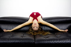 Femme attirante se penchant contre un sofa noir Photos stock