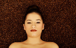Femme attirante se situant en graines de café Image stock