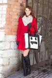 Femme attirante se tenant au-dessus du mur de briques rouge Image libre de droits