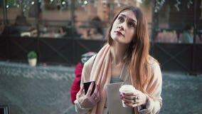 Femme attirante se tenant devant l'exposition-fenêtre et le thé potable La fille de brune rêve d'acheter quelque chose, soupire clips vidéos