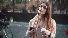 Femme attirante se tenant devant l'exposition-fenêtre et le thé potable La fille de brune rêve d'acheter quelque chose, soupire Image libre de droits