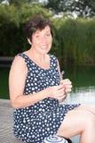 Femme attirante siiting avec des jambes dans la piscine et comptant la prairie Image libre de droits