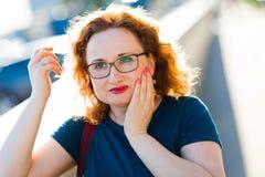 Femme attirante sur le mal soudain de dent de sentiment de rue photographie stock libre de droits