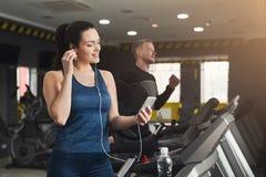 Femme attirante sur le tapis roulant dans le centre de fitness Photographie stock