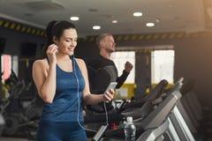 Femme attirante sur le tapis roulant dans le centre de fitness Images stock