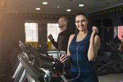 Femme attirante sur le tapis roulant dans le centre de fitness Photos stock