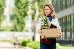 femme attirante tenant la boîte de papier avec la substance de bureau photos stock