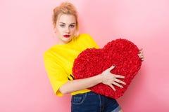 Femme attirante tenant le grand coeur rouge de fleur Images stock