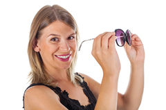 Femme attirante tenant ses lunettes de soleil - d'isolement Images libres de droits