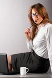 Femme au bureau avec l'ordinateur portatif Photographie stock libre de droits