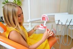Femme au bureau de dentiste apprenant comment s'inquiéter des dents Image libre de droits