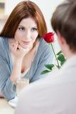 Femme au café avec la rose d'écarlate Images stock