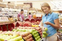 Femme au compteur de fruit dans le supermarché image libre de droits