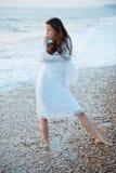 Femme au coucher du soleil sur la côte Photo stock