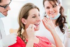 Femme au dentiste employant le fil dentaire photographie stock libre de droits