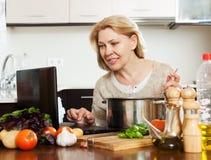 Femme au foyer à l'aide de l'ordinateur portable tout en faisant cuire Photo libre de droits
