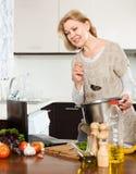 Femme au foyer à l'aide de l'ordinateur portable tout en faisant cuire la soupe Photos stock