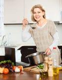 Femme au foyer à l'aide de l'ordinateur portable tout en faisant cuire la soupe avec le légume Photographie stock
