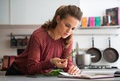 Femme au foyer étudiant les herbes fraîches d'épices dans la cuisine Photographie stock