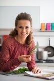 Femme au foyer étudiant les herbes fraîches d'épices dans la cuisine Photos stock