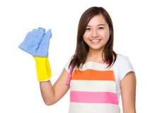 Femme au foyer asiatique avec le gant et le chiffon en plastique photo stock