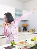 Femme au foyer asiatique dans la cuisine Photos stock