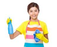 Femme au foyer asiatique employant le jet et le chiffon de bouteille avec les gants en plastique Images libres de droits
