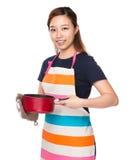 Femme au foyer asiatique tenant la casserole avec des gants de four photos libres de droits