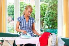 Femme au foyer avec du fer Photographie stock libre de droits